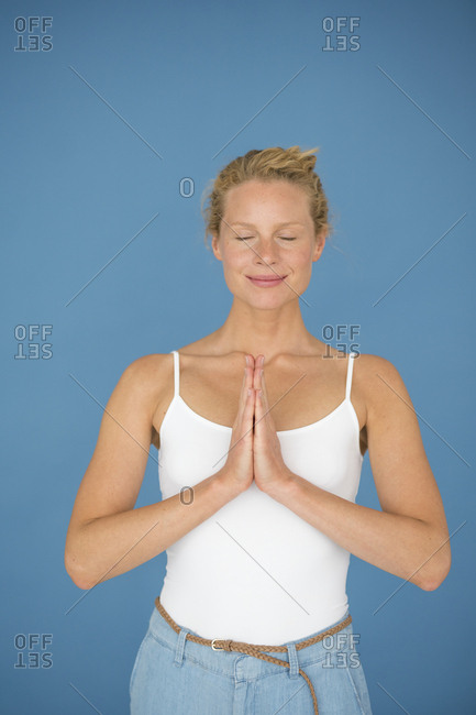 Smiling blond woman with closed eyes- concentrating