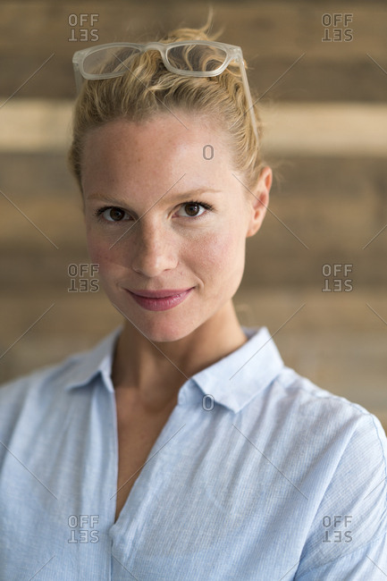 Portrait of blond woman- glasses- wooden background
