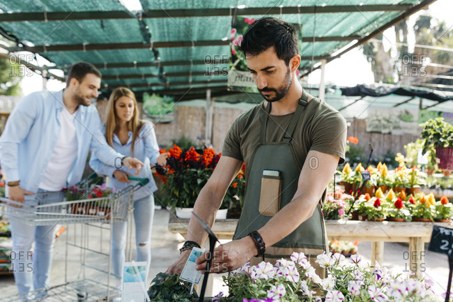 Worker in a garden center placing labels on flowers with customers in background