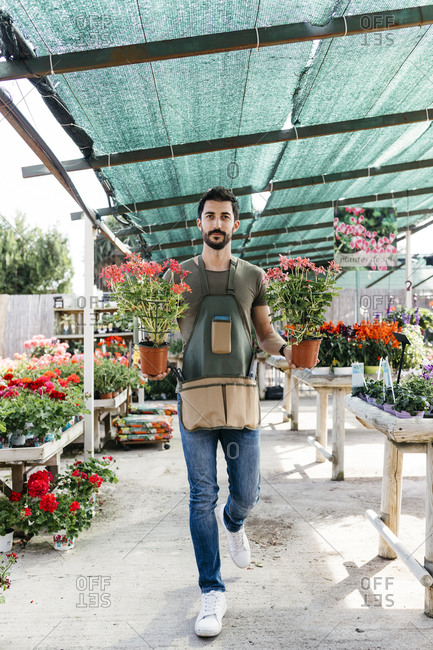 Gardener in a greenhouse holding flowers