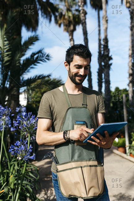 Smiling worker in a garden center using a tablet