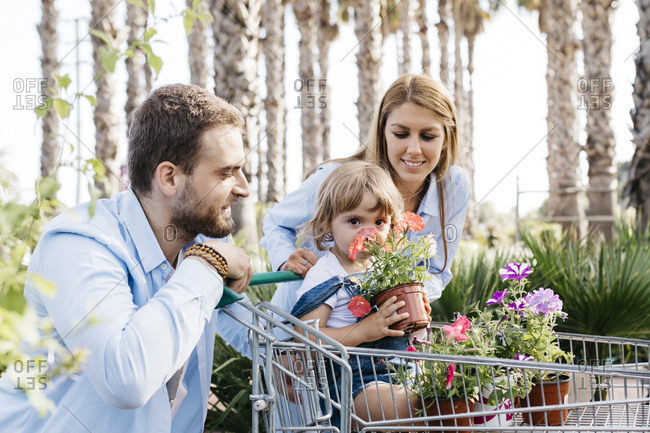 Family buying plants in a garden center with the daughter in shopping cart smelling at a flower