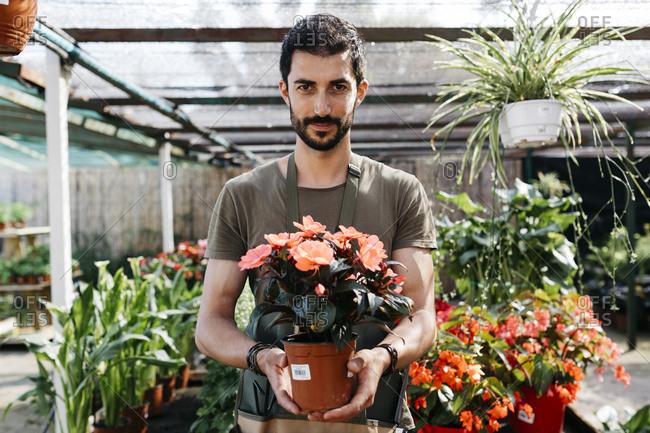 Portrait of a gardener in a garden center holding flower