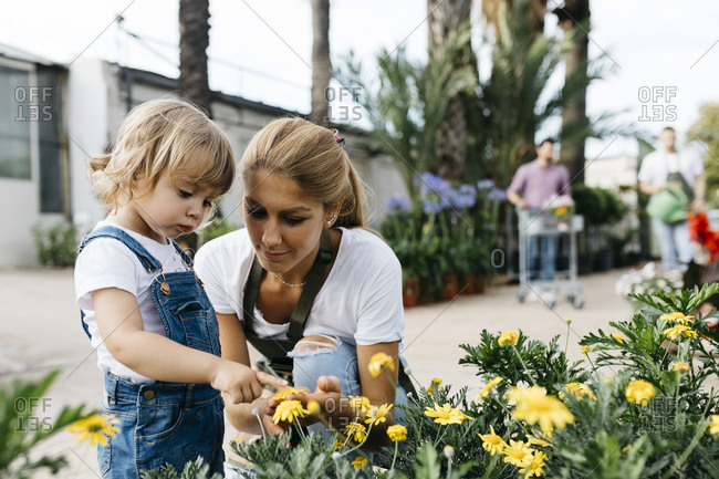 Female worker of a garden center showing flowers to a little girl