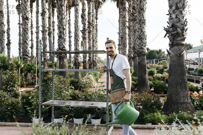 Worker in a garden center pushing a cart and holding watering can