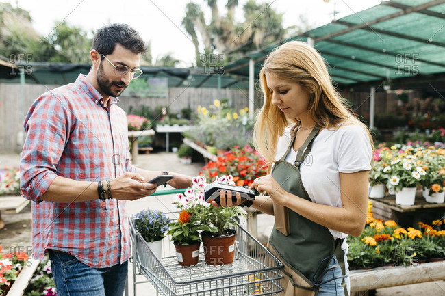 Customer paying with smartphone in a garden center