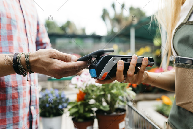 Close-up of customer paying with smartphone in a garden center