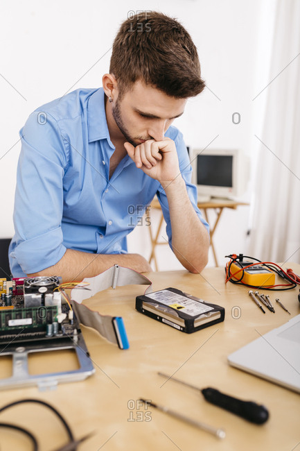 Technician repairing a desktop computer- thinking how to repair the hard drive