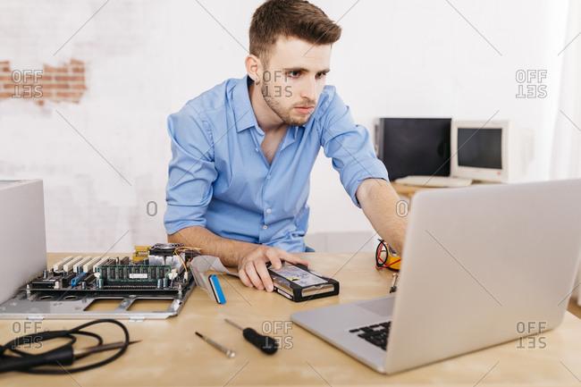 Technician repairing a desktop computer- using laptop