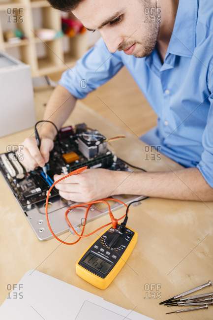 Technician repairing a desktop computer- checking the continuity of the plates and connectors