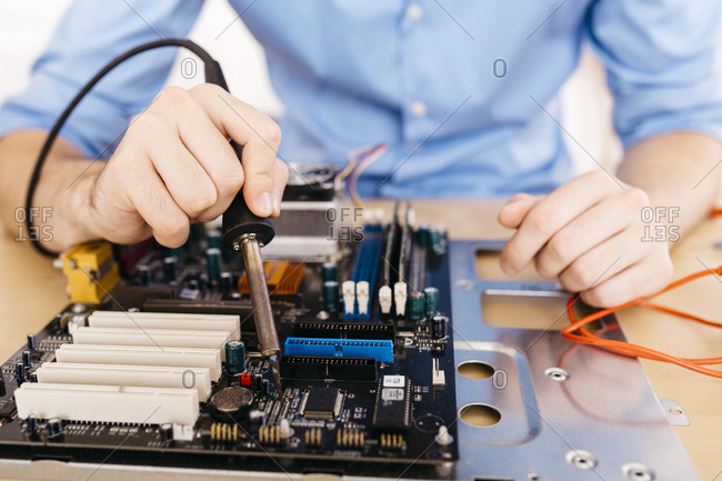 Close-up of technician repairing a desktop computer- soldering a component with tin