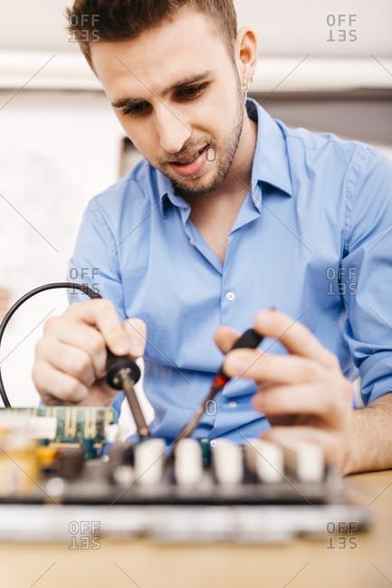 Technician repairing a desktop computer- soldering a component with tin