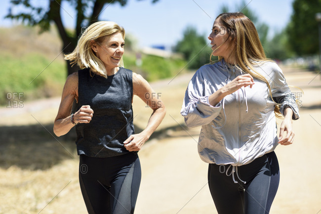 Mature woman running with her daughter in a park