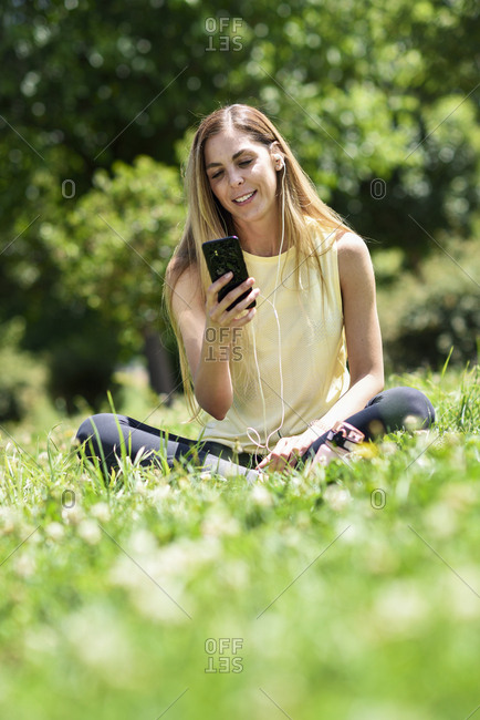 Woman using her smartphone- resting in the grass of a park after exercising