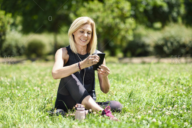 Mature woman using her smartphone- resting in the grass of a park after exercising