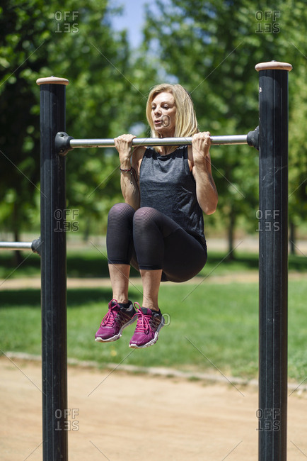Mature woman exercising at a bar in a park