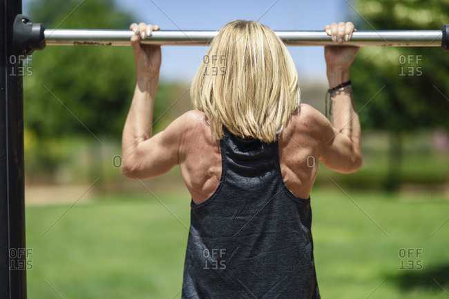 Rear view of mature woman exercising at a bar in a park