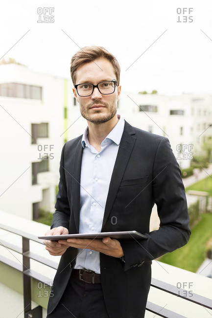Portrait of a businessman with tablet standing on balcony in a development area