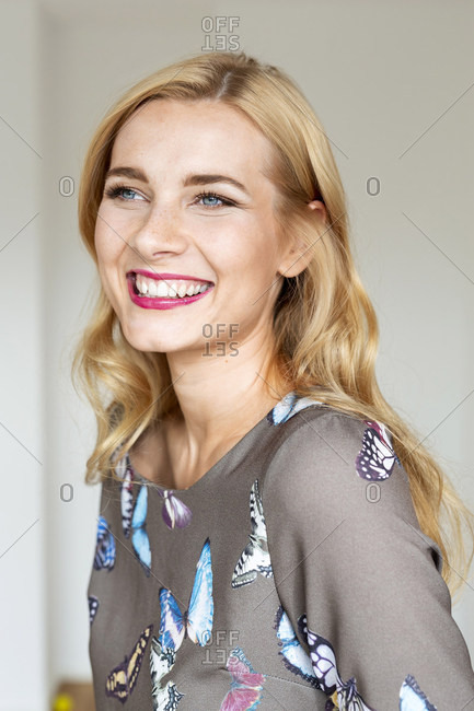Portrait of a happy young woman wearing a dress with butterfly imprint