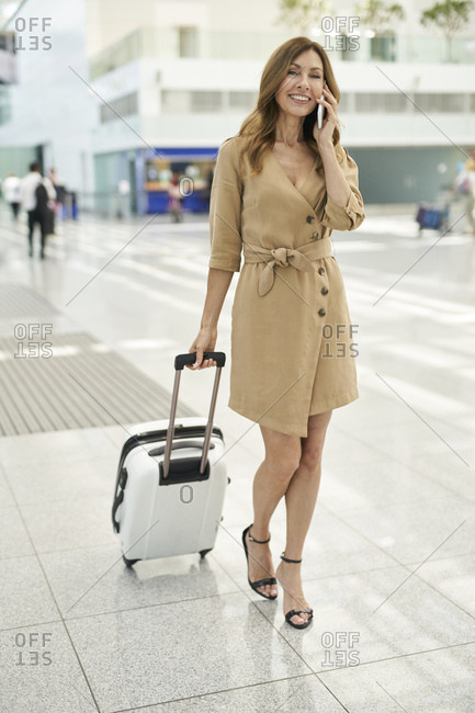 Businesswoman with suitcase- using smartphone