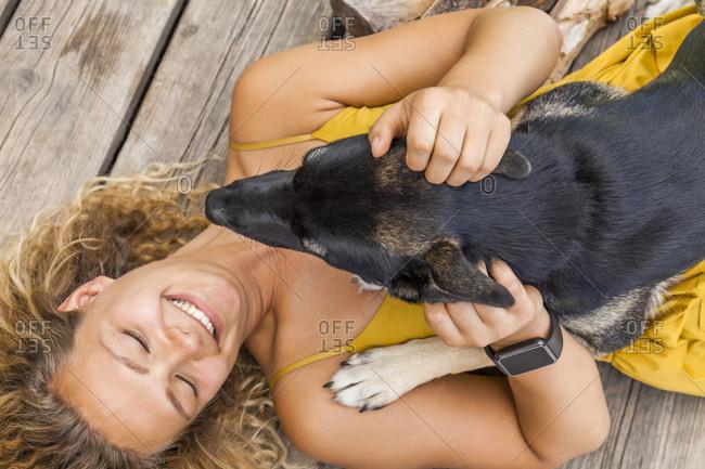 Husky shepherd mongrel dog and his mistress lying on wooden board