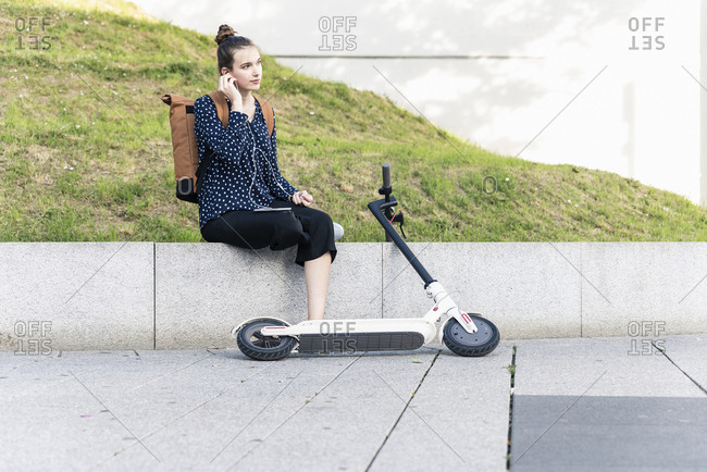 Young woman with electric scooter and earphones having a break