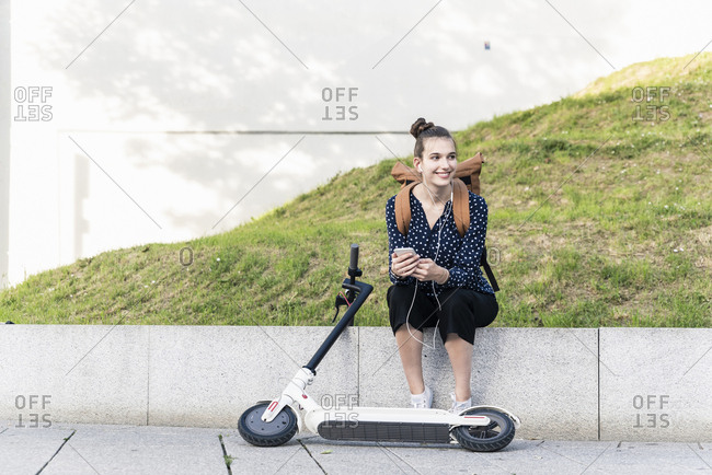 Smiling young woman with electric scooter- earphones and cell phone having a break