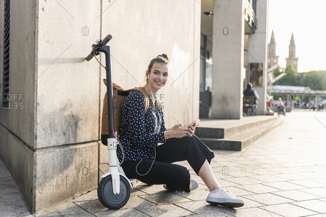 Smiling young woman with electric scooter- earphones and cell phone having a break in the city