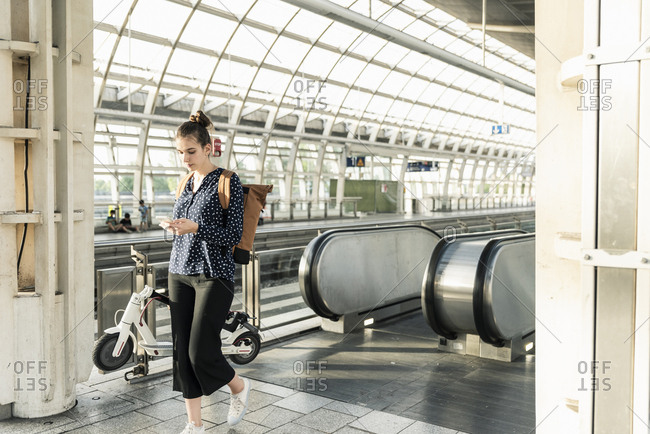 Young woman with electric scooter and cell phone at the train station