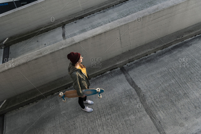 Stylish young woman with skateboard standing on parking deck
