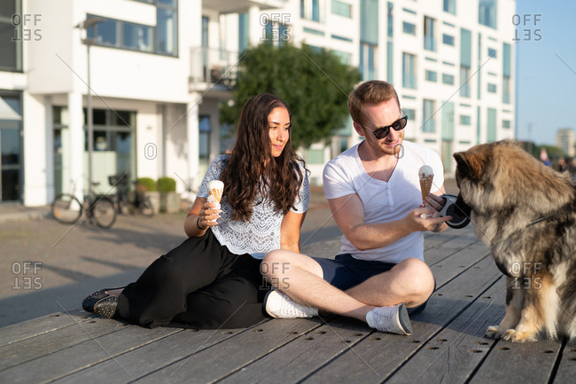 Couple on boardwalk with dog eating ice cream