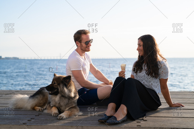 Couple on pier with dog eating ice cream