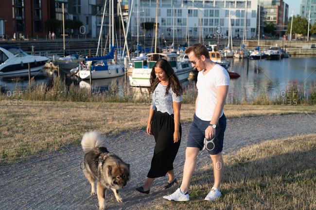 Couple walking dog near boat harbor
