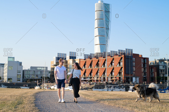 Couple walking dog near boat harbor in city