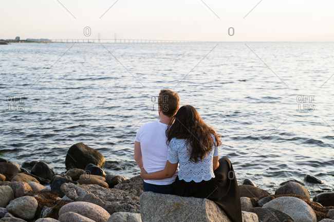 Rear view of happy couple snuggling on rocky coast at sunset