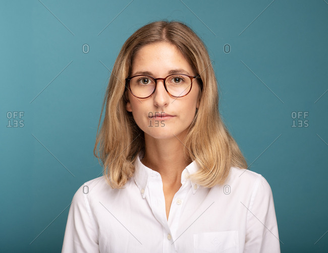 Portrait of a blonde woman with glasses in front of blue background
