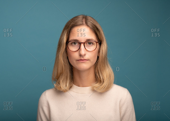 Portrait of a woman with glasses in front of blue background