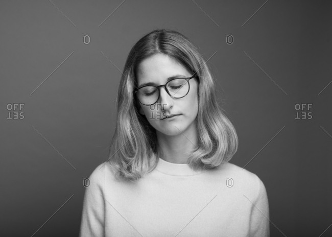 Portrait of a woman with glasses and her eyes closed in black and white