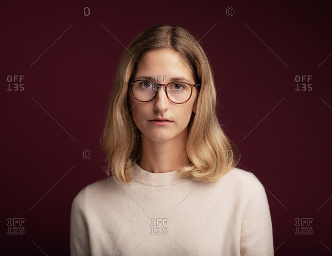 Portrait of a blonde woman with glasses in front of red background