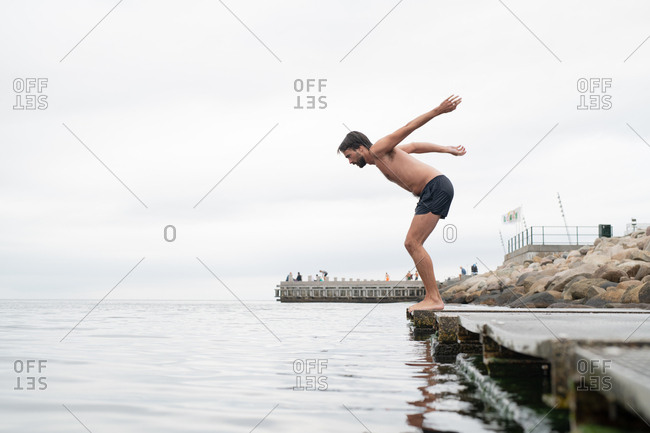 Man diving into sea from boardwalk