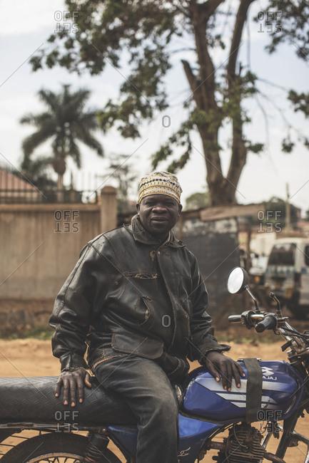 Kampala, Uganda - October 8, 2018: A smiling man on a motorbike