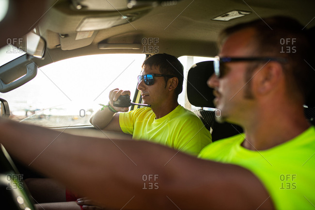 Partners, men and young lifeguards in the rescue vehicle talking to each other