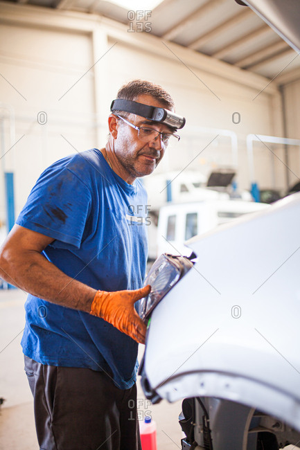 Middle-aged mechanic man repairing a car in his mechanic workshop