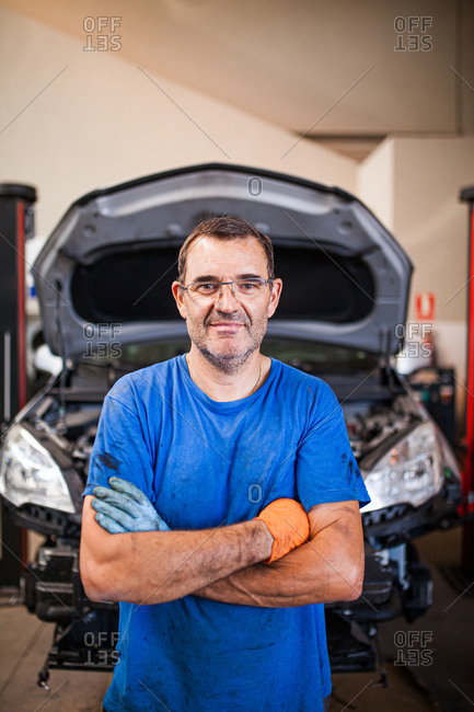 Middle-aged man with glasses repairing a car in his mechanic workshop, posing looking at the camera