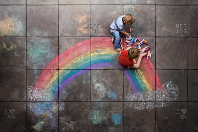 Two little boys drawing a rainbow with sidewalk chalk