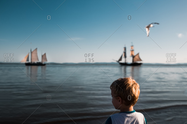 Little boy watching pirate ships in the ocean