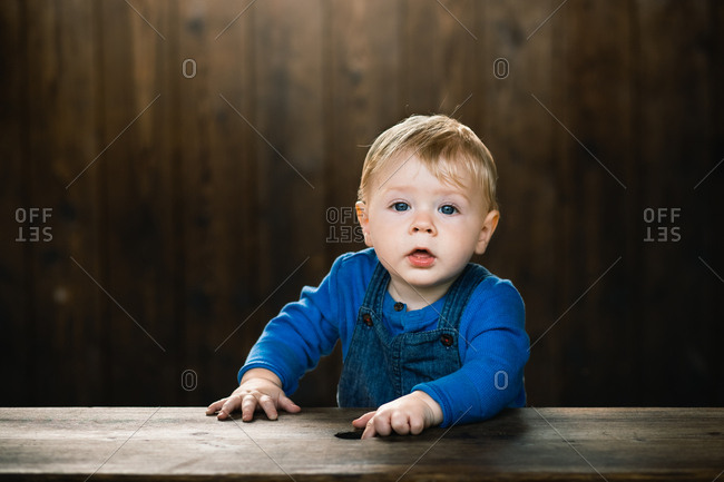 Portrait of a cute baby with blonde hair and blue eyes wearing overalls