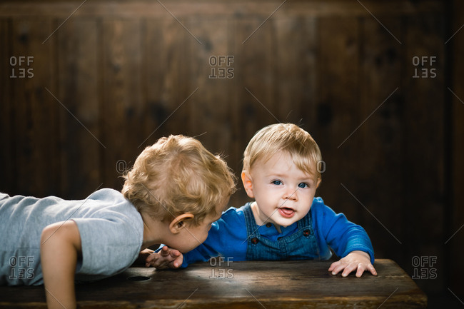 Brother leaning in to baby brother on wooden bench