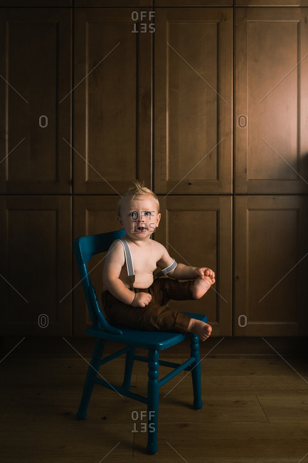 Cute baby boy wearing suspenders sitting on wooden blue chair
