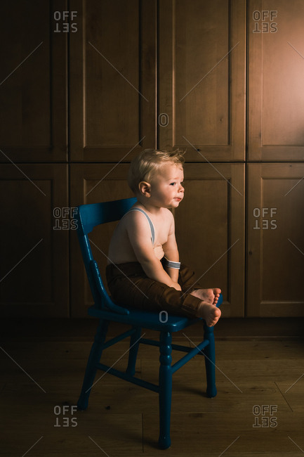 Profile of a cute baby boy wearing suspenders sitting on wooden blue chair